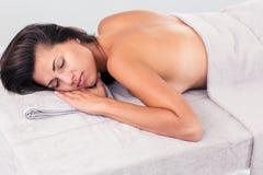 Расслабленная женщина лежа на lounger массажа стоковые фото