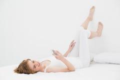 Расслабленная женщина смотря мобильный телефон в кровати Стоковая Фотография