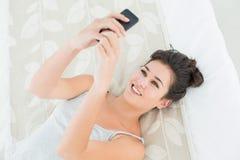 Расслабленная женщина смотря мобильный телефон в кровати Стоковое Изображение