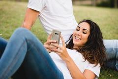 Расслабленная женщина с ее smartphone и парнем Стоковые Изображения