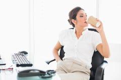 Расслабленная коммерсантка выпивая кофе на ее столе стоковые фото