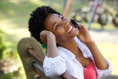 Расслабленная молодая африканская женщина говоря на мобильном телефоне Стоковое фото RF