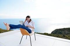 Расслабленная молодая женщина дома работая на компьтер-книжке стоковые фотографии rf