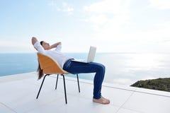 Расслабленная молодая женщина дома работая на компьтер-книжке стоковое фото