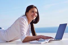 Расслабленная молодая женщина дома работая на портативном компьютере стоковые фото