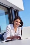 Расслабленная молодая женщина дома работая на портативном компьютере стоковое изображение