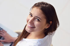 Расслабленная молодая женщина дома работая на портативном компьютере стоковая фотография rf