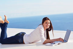 Расслабленная молодая женщина дома работая на портативном компьютере стоковые изображения rf