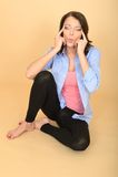 Расслабленная молодая женщина сидя на поле вытягивая выражения лица Стоковая Фотография RF