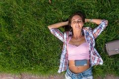 Расслабленная молодая женщина с наушниками слушая к музыке от smartphone и лежа на траве она глаза закрыло Стоковые Фотографии RF