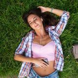 Расслабленная молодая женщина с наушниками слушая к музыке от smartphone и лежа на траве она глаза закрыло Стоковая Фотография RF