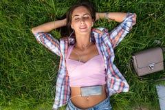 Расслабленная молодая женщина с наушниками слушая к музыке от smartphone и лежа на траве она глаза закрыло Стоковая Фотография