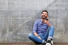 Расслабленная середина постарела человек сидя против стены Стоковое Изображение