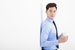 Расслабленная склонность бизнесмена против белой стены в офисе Стоковые Изображения