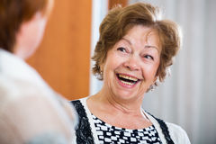 Расслабленные женские пенсионеры беседуя и усмехаясь крытые Стоковая Фотография