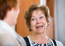 Расслабленные женские пенсионеры беседуя и усмехаясь крытые Стоковое фото RF