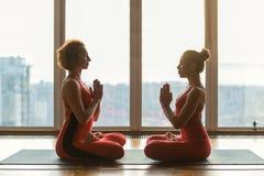 Расслабленные женские yogis размышляя около окна Стоковое Изображение