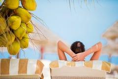 Расслабленные молодые женщины лежа на lounger пляжа около кокосовой пальмы Стоковые Фотографии RF