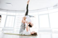 Расслабленные молодые пары балансируя и делая йогу acro стоковая фотография rf