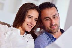Расслабленные молодые пары работая на портативном компьютере дома стоковое изображение rf