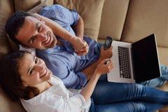 Расслабленные молодые пары работая на портативном компьютере дома стоковое фото