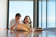Расслабленные молодые пары работая на портативном компьютере дома Стоковые Изображения RF