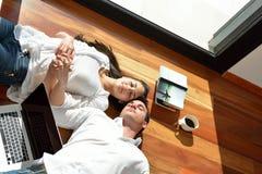 Расслабленные молодые пары работая на портативном компьютере дома Стоковое Изображение