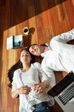 Расслабленные молодые пары работая на портативном компьютере дома Стоковая Фотография