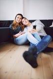 Расслабленные подростковые пары смотря ТВ дома стоковое фото rf