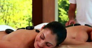 Расслабленные друзья наслаждаясь горячими каменными массажами сток-видео