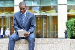 Расслабленный бизнесмен используя его ПК таблетки стоковая фотография rf