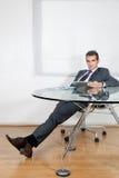 Расслабленный бизнесмен используя таблетку цифров в офисе Стоковые Фото