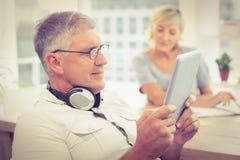Расслабленный бизнесмен смотря его таблетку Стоковое фото RF