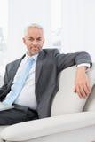 Расслабленный зрелый бизнесмен с компьтер-книжкой дома Стоковое Изображение RF