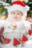 Расслабленный маленький santa сидя в плетеной корзине Стоковая Фотография