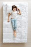 Расслабленный мальчик лежа в кровати с сигналом тревоги Стоковые Фотографии RF