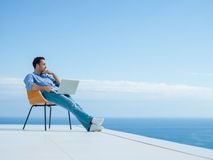 Расслабленный молодой человек дома на балконе стоковое изображение rf