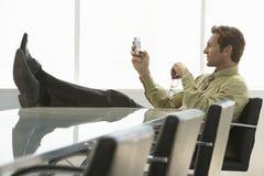 Relaxed обмен текстовыми сообщениями бизнесмена на сотовом телефоне в конференции r Стоковая Фотография RF