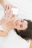 Расслабленный обмен текстовыми сообщениями молодой женщины в кровати Стоковое Изображение RF