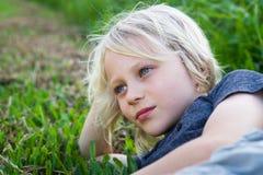 Расслабленный ребенок outdoors лежа на траве Стоковое фото RF