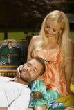 Расслабленный человек лежа в подоле счастливой женщины на пикнике Стоковые Фотографии RF