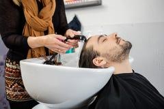 Расслабленный человек имея волосы быть помытым в салоне красоты стоковая фотография rf