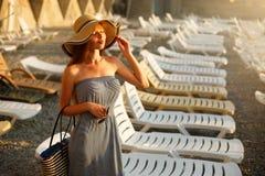 Расслабляющая женщина наслаждаясь положением солнца лета счастливым в широкой шляпе солнца на пляже при сторона поднятая к солнеч Стоковые Изображения RF