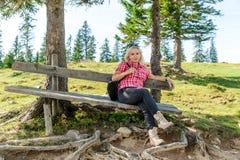 Расслабляющая женщина на деревянной скамье стоковые фото