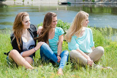 Расслабляющая красивая женщина 3 сидит на зеленой траве Стоковая Фотография