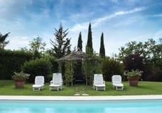 Расслабляющее положение бассейном под голубым небом Стоковое Изображение RF