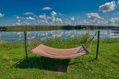 Расслабляющий гамак на береге озера под солнечностью лета стоковое фото rf