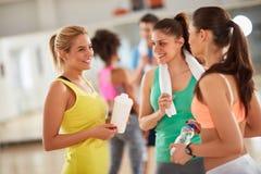 Расслабляющий переговор после тренировки между усмехаясь девушками Стоковое фото RF