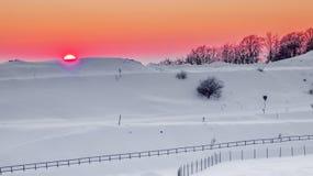 Расслабляющий теплый заход солнца в снежном ландшафте стоковая фотография