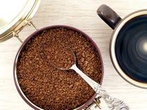 Растворимый кофе в алюминиевой чонсервной банке и черном кофе в чашке стоковые фото